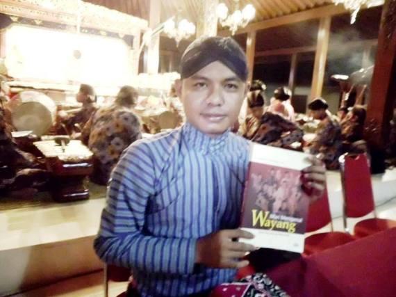 "Ki Sumanto Susilamadya memegang buku "" Mari Mengenal Wayang "" karyanya."